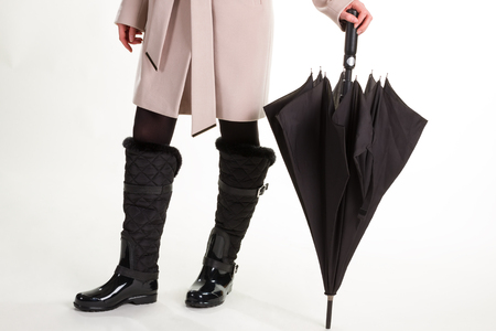 Autumn clothes. Woman in rubber boots with black umbrella. Stock Photo