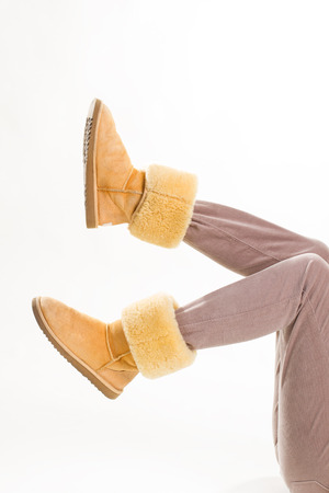 Girl in funny yellow winter boots and beige pants.