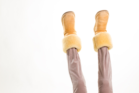 Female feet in winter yellow shoes lifted up. Imagens