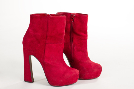 Pair of bright suede shoe with high heels. Sexy womens shoes on a white background. Bright red ankle boots.
