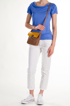 Light spring outfit and purse. White trousers and brown purse. Cotton t-shirt and leather purse. Casual style for warm season.