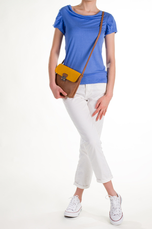 Female model in casual outfit. White gumshoes and brown purse. Small brown leather purse. Young woman in casual style.