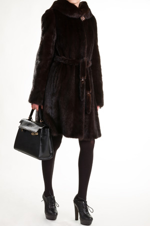 Woman in brown furcoat. Female model in luxury outfit. Expensive clothes for a woman. Winter outfit in boutique. Standard-Bild