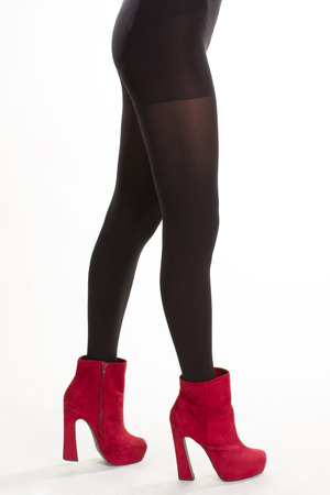 Model wearing red ankle boots. Black pantyhose and red footwear. Cherry suede ankle boots. Bright shoes and black tights.