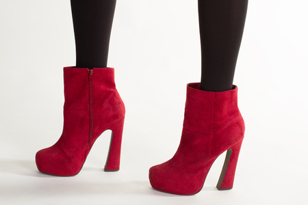 Womans suede shoes. Close-up of bright footwear. Sexy legs in cherry ankle boots. Elegant suede ankle boots. Stock Photo