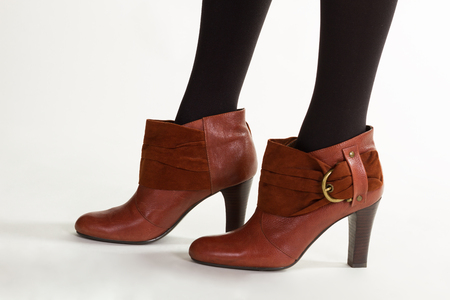 Brown leather ankle boot. Shoes with thin nubuck straps. Model in brown ankle boots.