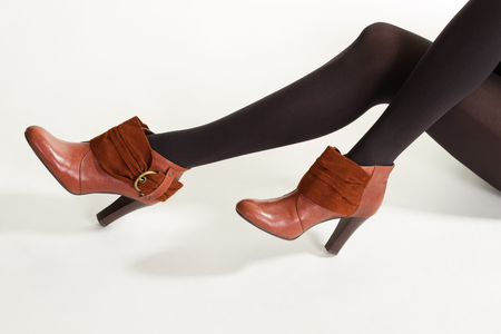 Slim model wears brown shoes. Brown ankle boots with insets. Black tights and brown footwear. Dark pantyhose with brown shoes.