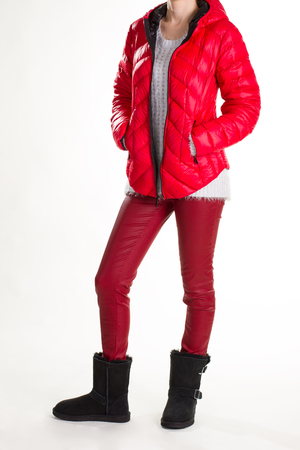 Woman in warm clothes. Model in red winter jacket. Red padded down jacket. Leather pants and red jacket.