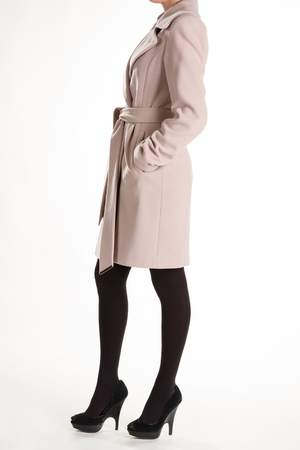 Slim woman wearing beige coat. Beige cashmere coat. Light spring cashmere coat. Beige coat and black tights.