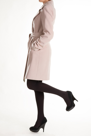 High heels and light coat. Black shoes with beige coat. Dark pantyhose and cashmere coat. Womans conservative style.