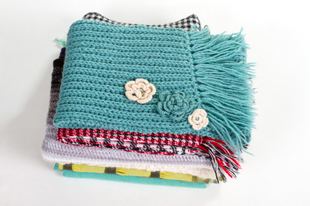 Stack of beautiful knitted winter scarves. Warm handmade scarfs. Stock Photo