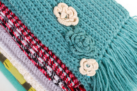Beautiful crocheted flowers on the scarf. Many different scarves in a pile. Stock Photo