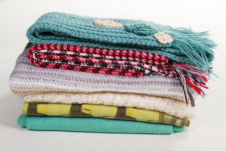 Stack of different winter scarves. Knits and knitted scarfs on a white background. Winter accessories.