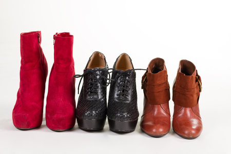 Beautiful autumn ankle boots in different colors. Red, black and brown leather boots. Stock Photo