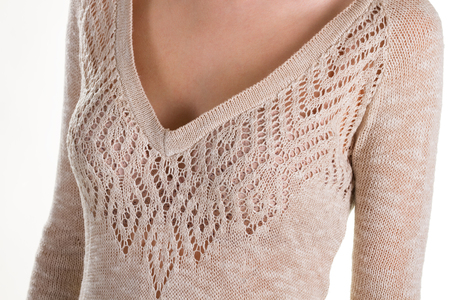 Beautiful knitted blouse on a woman's body. Decollete of the young girl. Openwork knitting. Stock Photo