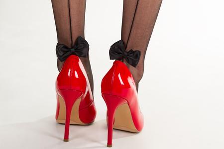 Rood lakken schoenen met hoge hakken. Mooie zwarte sexy kousen met strikken.