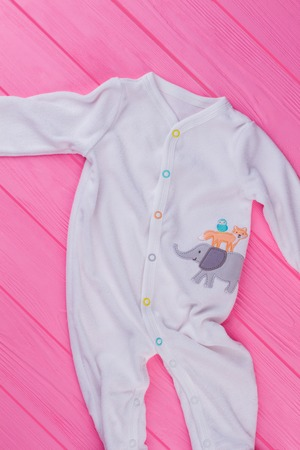 Top view white baby pajamas. Pink wooden background. Top view. Banque d'images - 113219295