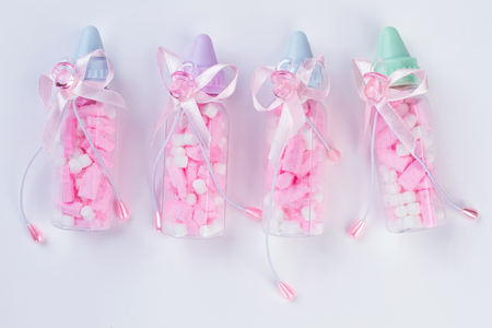 Four baby bottles with pills or sweets and bows. White isolated background.