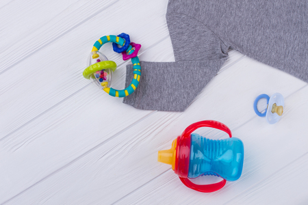 Baby cloth and toys on wood. Newborn kids necessities. Rattle, bottle and pacifier. Banco de Imagens