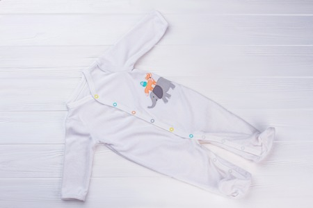 White footed baby pajama on wood. White wood background. Stock Photo