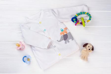 Maglietta morbida bianca e giocattoli. Sonaglio, peluche per cani e ciucci su legno.