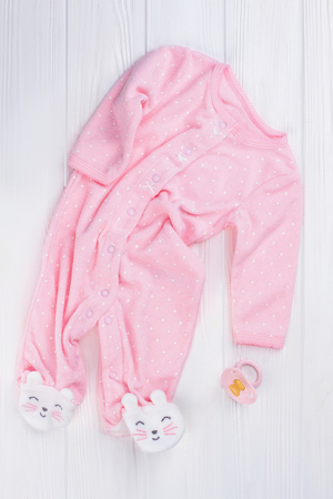 Pink baby sleeper pajama with kitties legs and pacifier. White wood background.