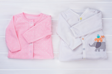 Folded baby clothes, top view. Pink and white sleepwear toddler shirts on white wood. Stock Photo