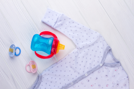Blue baby bottle, pacifiers and clothes. White wood background. Archivio Fotografico