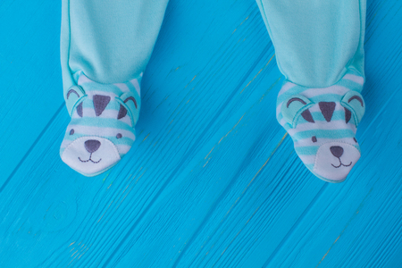 Footie pajamas for baby boys sleep. Close up. Blue wood background. Stock Photo