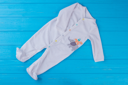 White printed footie baby pajama. Top view. Blue wood background. Banque d'images - 113223983