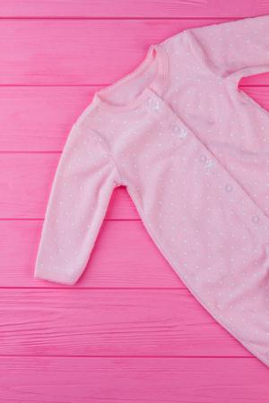 Pink baby sleepwear on pink wood. Cropped image of pajamas, top view. 스톡 콘텐츠