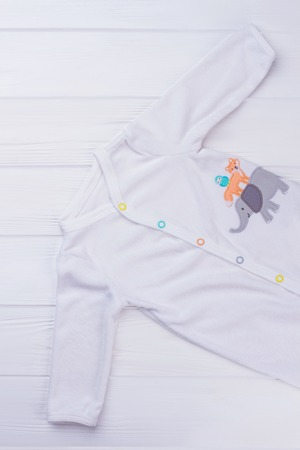 White kid pajama with cartoon image. Top view. White wood background. Banque d'images - 119813988
