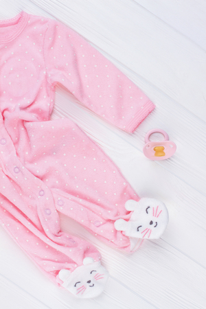 Pink fleece pajama and pacifier. Kitties feet. White wood background.