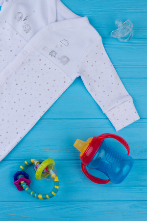 Cut-out kid clothing. Close up baby nipple, rattle and bottle. 스톡 콘텐츠