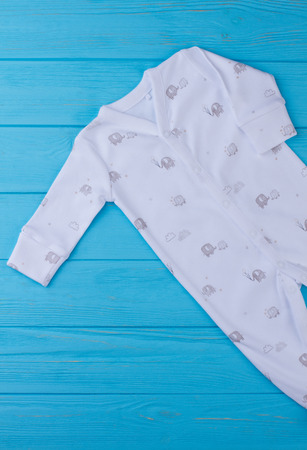 Sleeve of infant boy clothing, top view. Cot-our cotton baby sleeper on blue wood background.