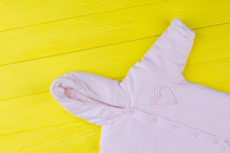 Close up baby girl fleece coverall. Pink baby cloth hood on yellow table. Stock Photo