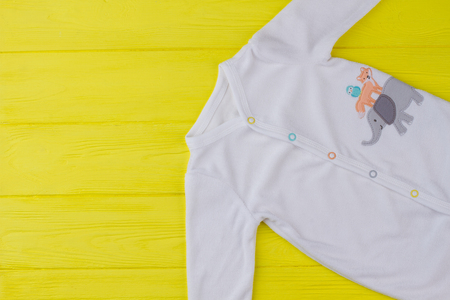 Close up top view white baby shirt. Cropped image of child wear in yellow background.