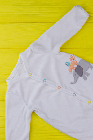 Funny cartoon image on white baby cloth. Sleepwear cloth for kids in yellow background, top view. Stock Photo