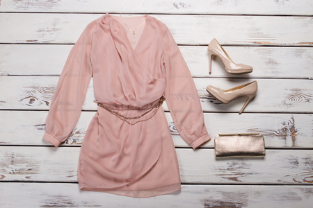 Peach dress and red heels. Evening apparel on wooden showcase. Womans outfit with glossy heels. Huge discounts for clothing.