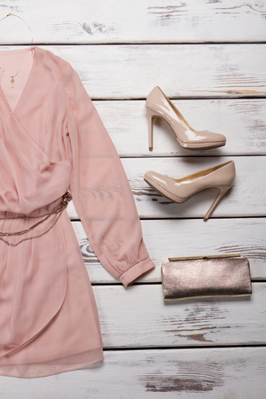 Peach dress and clutch bag. Shelf with dress and purse. Girl's luxury accessory and clothing. Trendy outfit in boutique.