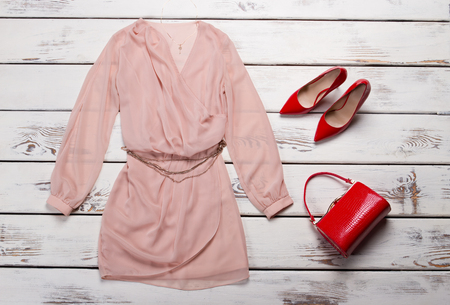 Red heels with peach dress. Dress and heels on showcase. Female evening clothes for summer. New apparel in clothing store. Zdjęcie Seryjne