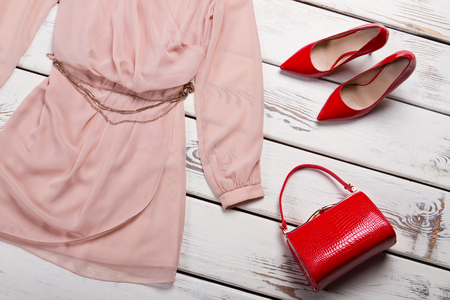 Red glossy bag and dress. Bright red purse on table. Young ladys luxury handbag. Glossy leather accessory on sale.