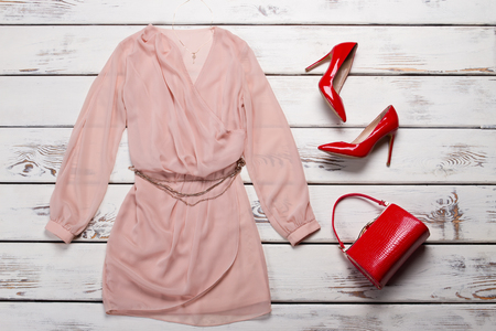 Peach dress with glossy heels. Red heel shoes on showcase. Glamorous evening outfit for women. Summer sale at fashion store.