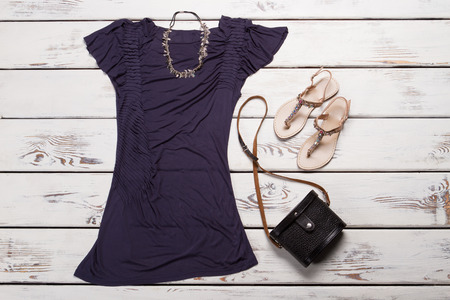 Purple t-shirt and beige sandals. T-shirt and footwear on shelf. Womans casual dark t-shirt. Simple top for summer.