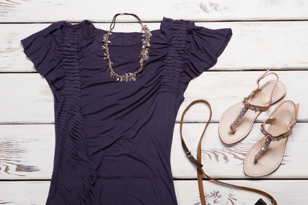 Purple t-shirt and necklace. Table with t-shirt and accessory. Ladys bijouterie necklace on display. Casual apparel in fashion store. Zdjęcie Seryjne