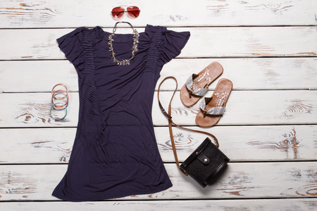 Purple dress with accessories. Top and sunglasses on display. Girls dark-colored casual top. Stylish accessories from new catalog.