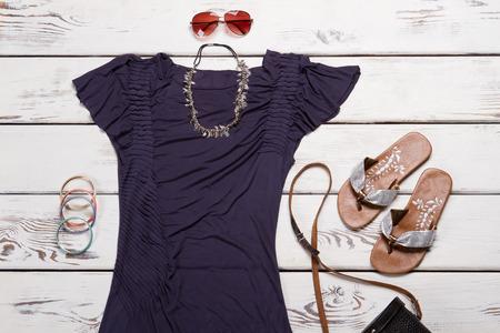 T-shirt and flip flops. Stylish flip flops on shelf. Ladys trendy sunglasses and bracelets. Casual garment of dark color.