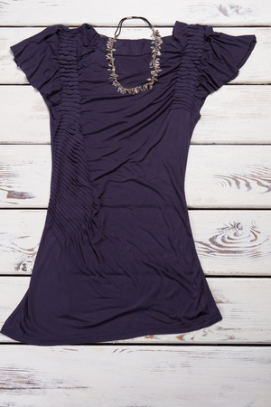Dark purple dress and necklace. Dark t-shirt on white table. Womans dark summer top. Fashionable t-shirt at low price.