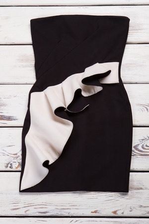 Black evening dress with applique. Black dress on white table. Womans dark charming dress. Merchandise from new collection. Zdjęcie Seryjne