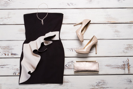 Black dress and beige heels. Dark evening dress on shelf. Female evening apparel with footwear. Luxury outfit in local store.